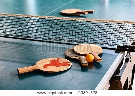 Old used table tennis rackets on the game table