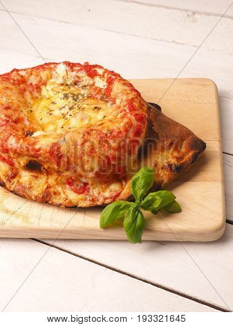 Tasty pizza calzone on a wooden cutting board