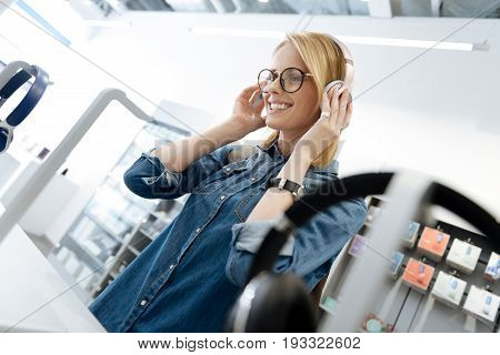 Smiling female shopper wearing casual attire standing at a display while shopping for a new pair of headphone at a department store.