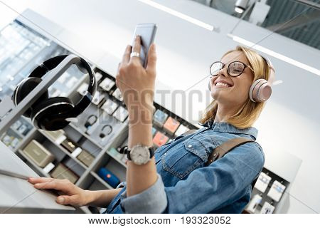 Extremely happy female shopper wearing glasses grinning widely while leaning on a display of a local shop and trying out her new pretty headphones.