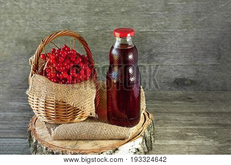 Berries of viburnum in a basket on a napkin next to the glass transparent bottle of juice. Rustic. The horizontal frame.