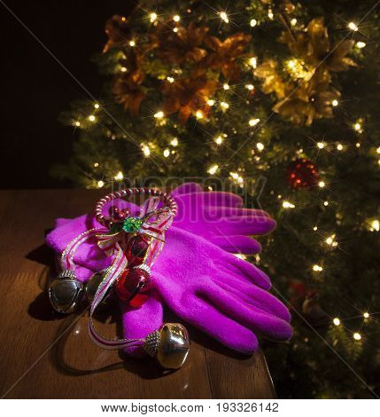 New pink gloves for Christmas with bells on a table