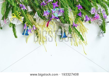 row of christmass tree brunches decorated with a bells and bell flowers, copy space for your text at the bottom. new year and christmas conceptual greeting card.