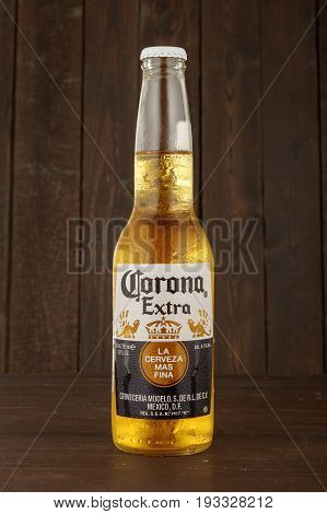 MINSK, BELARUS - JUNE 29, 2017: Editorial photo of bottle of Corona Extra beer on wooden background, one of the top-selling beers worldwide is a pale lager produced by Cerveceria Modelo in Mexico.