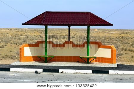 Stopping place of public transport with a metal tent on a road in oriental desert area