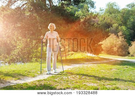 Outdoor activity. Joyful positive elderly woman holding Nordic walking poles and hiking while being in the park