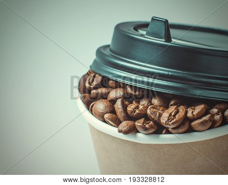 Paper Coffee cup with Coffee Beans background. Takeaway or Disposable Coffee Cup retro toning