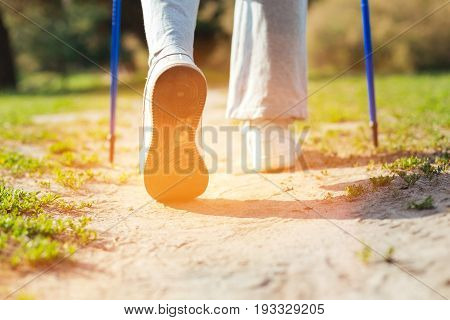Movement is life. Close up of a person holding Nordic walking poles and going forward while being in the park