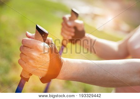 Pleasant activity. Close up of a hand of a sporty active man holding a walking pole and practicing Nordic walking while staying healthy
