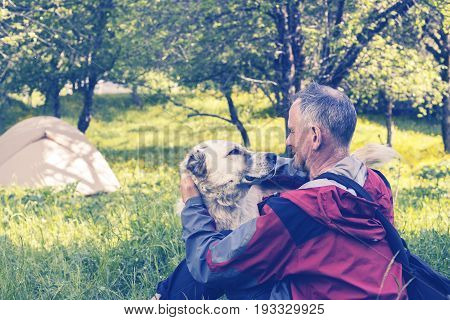 Man Traveler Is Playing With The Big Dog In A Camp