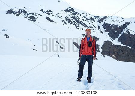 Tired Traveler Stands On The Snow-capped Mountain Slope