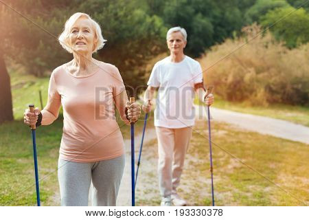 Walking activity. Nice pleasant elderly woman holding poles and walking while enjoying this activity