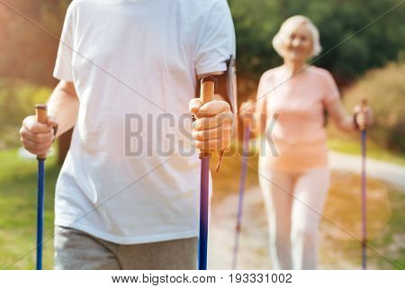 Training equipment. Close up of a mans hand holding the walking poles and moving forward while being in the park