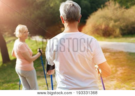 Sports activities. Nice handsome well built man holding walking poles and looking at his wife while following her
