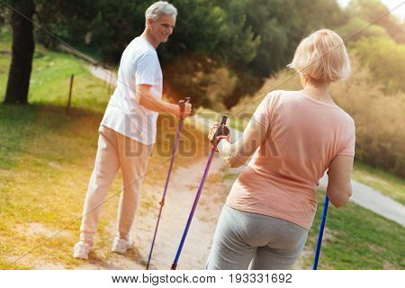 Our route. Nice pleasant senior couple holding walking poles and following the footpath while exercising in the park