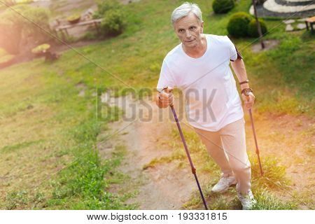 Fresh air. Pleasant active senior man holding walking poles and going up the hill while being outdoors