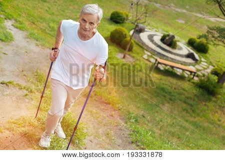 I can do it. Serious confident elderly man going up the hill and looking forward while doing sport activities