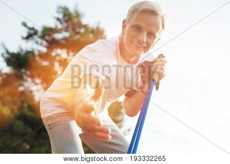 Help and support. Positive handsome senior man holding walking poles and smiling while offering you his hand