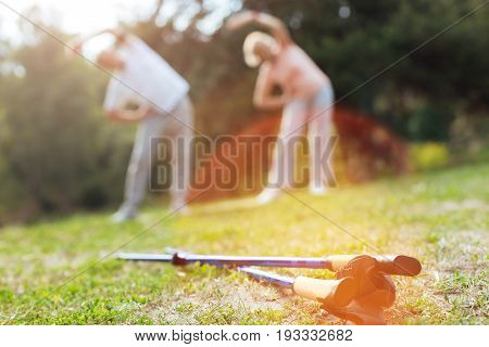Nordic walking poles. Professional sports equipment lying on the ground with nice sporty good looking people doing physical exercises in the background
