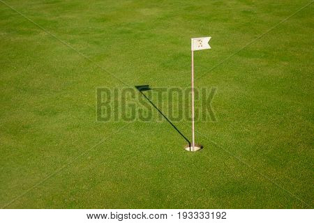 Glof flag mark in hole throwing shadow on the green course grass, golf playing concept