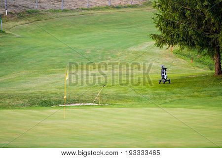 Golf course with one green with flag pole, a bunker and trolley on the fairway