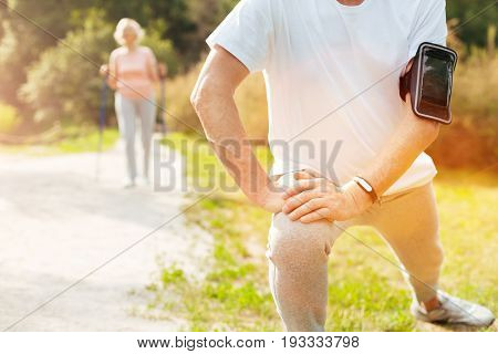 Morning workout. Close up of a nice well built aged man doing a physical exercise while having a morning workout