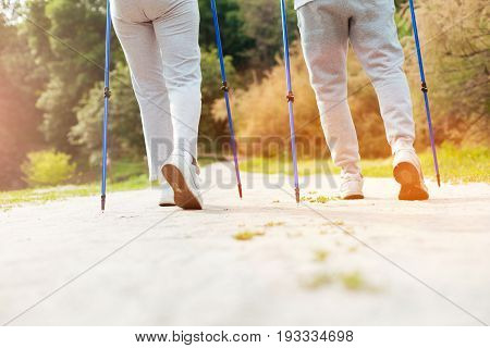 In synch. Sporty nice elderly couple holding Nordic walking poles and going forward while exercising together
