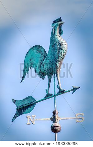 Big on a weathervane. Metal Weathercock pointing south west. Blue green weather vane showing wind direction.
