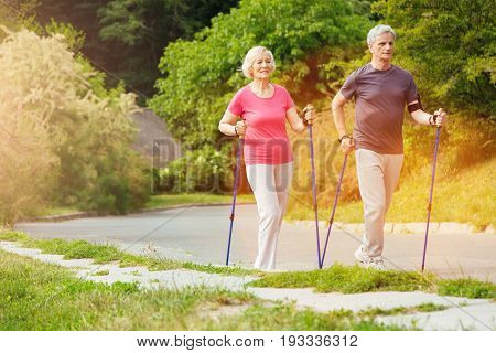 Our walking route. Positive sporty nice couple walking along the road and smiling while using walking poles