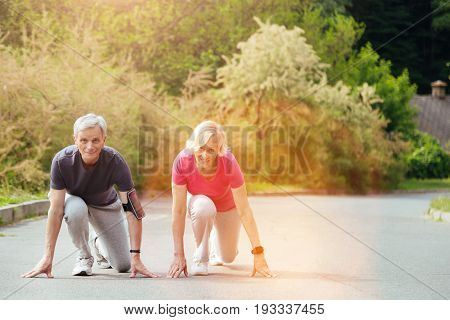 Crouch start. Positive active senior couple sitting in the special position and preparing to run while having an outdoor training