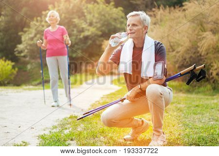Preventing dehydration. Joyful well built senior man smiling and drinking water while holding Nordic walking poles