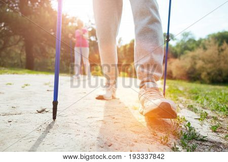 Step forward. Close up of a nice well build sporty man making a step and moving forward while using Nordic walking poles