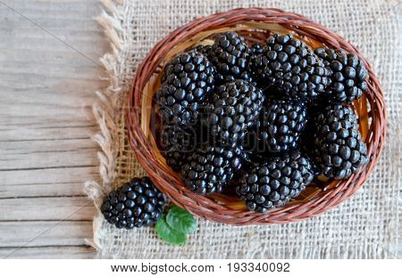 Ripe blackberries in a basket on burlap cloth on old wooden background.Blackberry.Healthy food or diet concept.Selective focus.