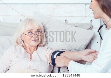 Full of responsibility. Positive smiling young caregiver sitting in the bedroom and helping old woman while measuring her blood pressure
