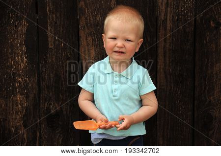 A cute kid plays with a scoop in a sandbox on a rural backyard in a hot summer evening