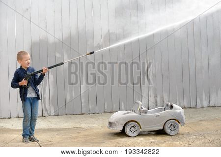 A young вгву plays with a car wash hose and a race prize in a rural compound in a hot summer