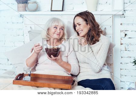 Love my grandmother. Positive merry young woman sitting at home and taking care of retired grandmother while pensioner enjoying breakfast