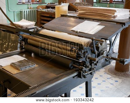 An old Book printing machine with piles of paper and a writing-board