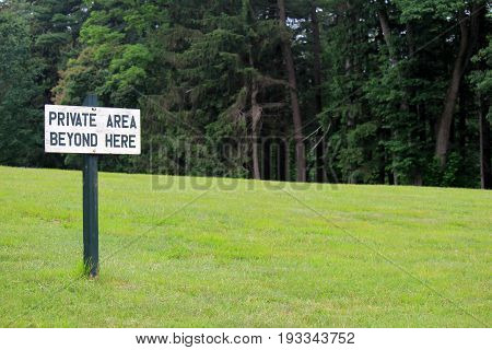 Horizontal image of hand painted sign that reads 'Private area beyond here.' with mown lawn and row of trees just beyond.