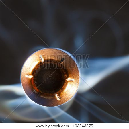 Hollow pont bullet with smoke behind coming at the camera
