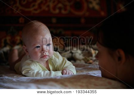 The child looks at his mother from the opposite side in the village house in the ragar of summer
