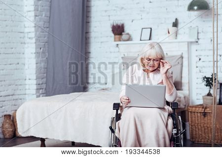 Enjoying modern technologies. Concentrated elderly enable woman sitting in the wheelchair at home while expressing positivity and using laptop
