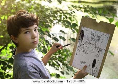 teenager artist boy make draft sketch of pond lake in the forest close up photo