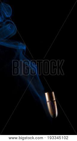 Copper plated bullet falling with blue smoke behind