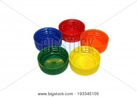 Bottlecaps in rainbow colors arranged in the shape of a flower. Isolated on white background.