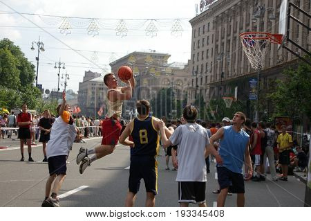 KYIV, UKRAINE - 28 JUNE 2012: Men playing street basketball at Khreschatyk Street in Kyiv, Ukraine 28 June 2012. Difficult jump shot with the resistance of the defenders in the open competitions on streetball