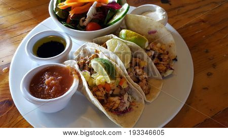 ISLAND FISH TACOS: blackened island fish flour tortilla mixed cabbage black bean chipotle aioli tropical fruit salsa red salsa sour cream and side salad on wood table