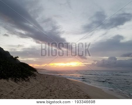 Beautiful Sunset over the ocean with waves moving to shore of Camp Edrman Beach on the North Shore of Oahu.