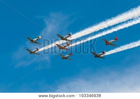 EDEN PRAIRIE MN - JULY 16 2016: Seven AT6 Texan airplanes fly left against cloudy sky with smoke trails at air show. The AT6 Texan was primarily used as trainer aircraft during and after World War II