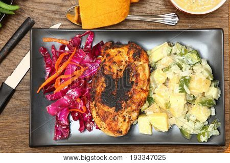 Cajun Spiced Chicken with potato salad and red cabbage slaw.